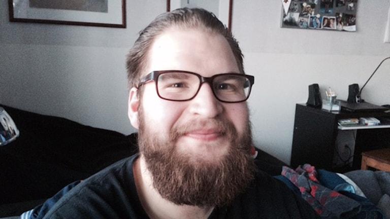 Han har skägg och glasögon. Håret är bakåtkammat.