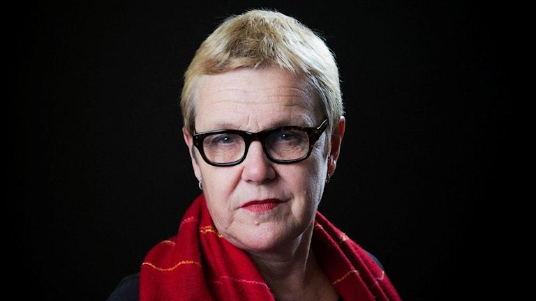 Elle-Kari Höjeberg har kortklippt blont hår, glasögon och en röd sjal.
