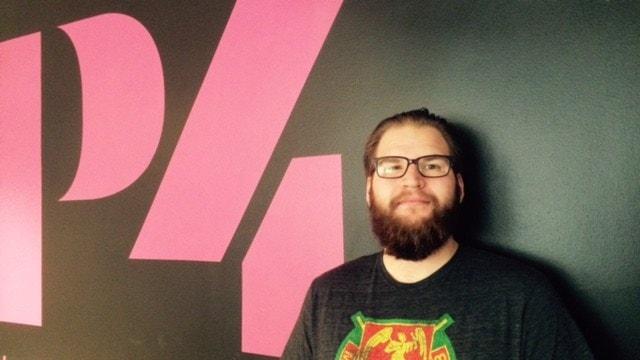 En kille i t-shirt och glasögon vid en P4 skylt