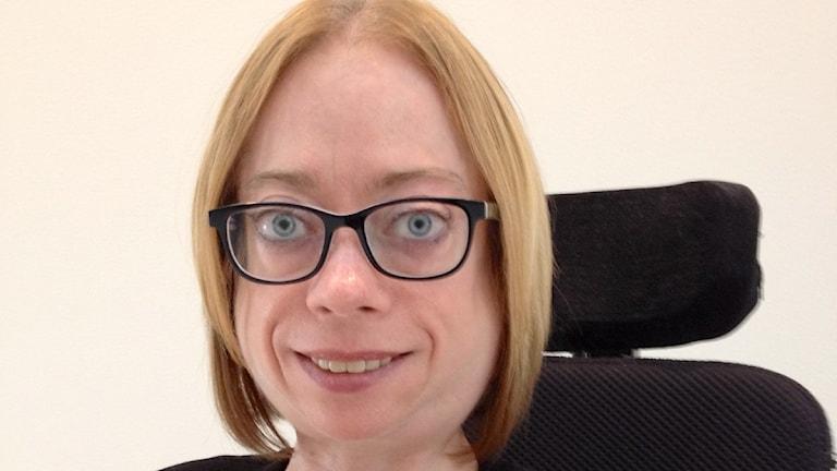 Hon har glasögon och håret är klippt i en pagefrisyr.