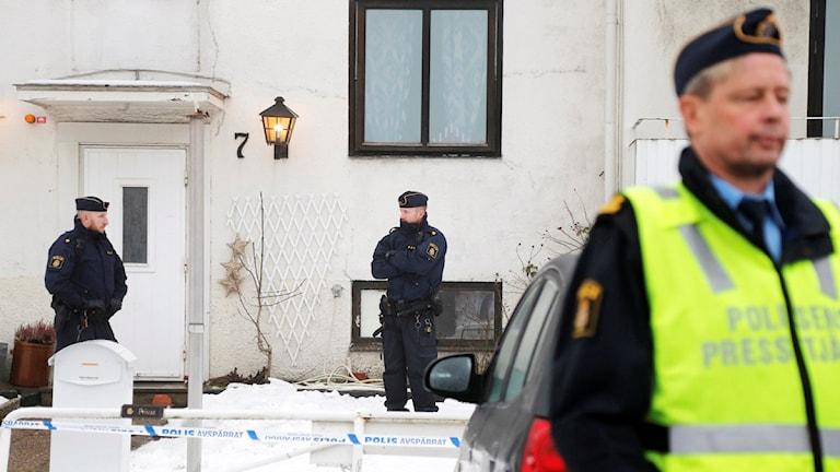 Det är ett vitt hus. tre poliser står utanför dörren.