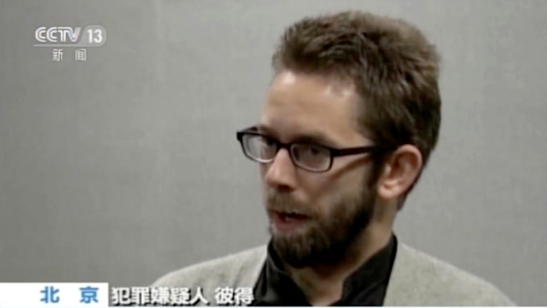Han har glasögon och skägg. I bilden syns också en text på kinesiska.