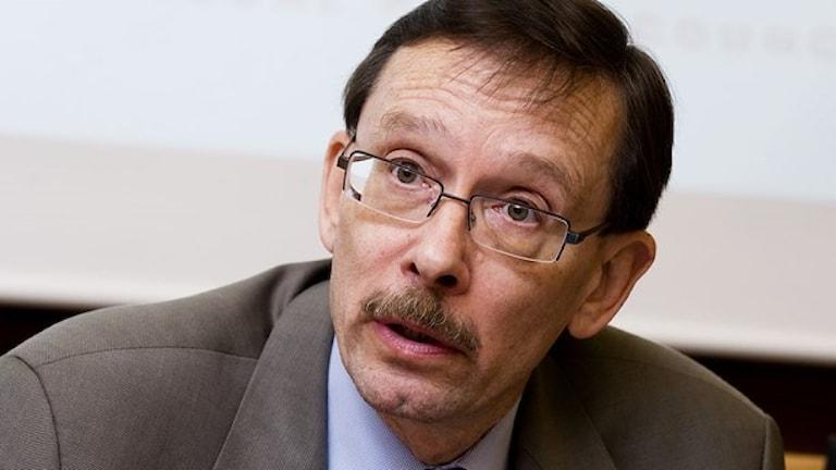 En man med kort brunt hår och glasögon