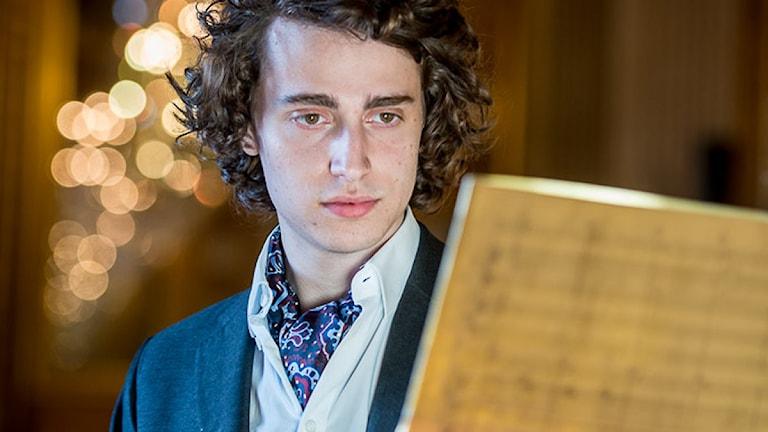 Jacob Mühlrad är klädd i blå kavaj och vit skjorta. Runt halsen har han en blå näsduk. Håret är stort och lockigt. Han håller i ett papper med noter.