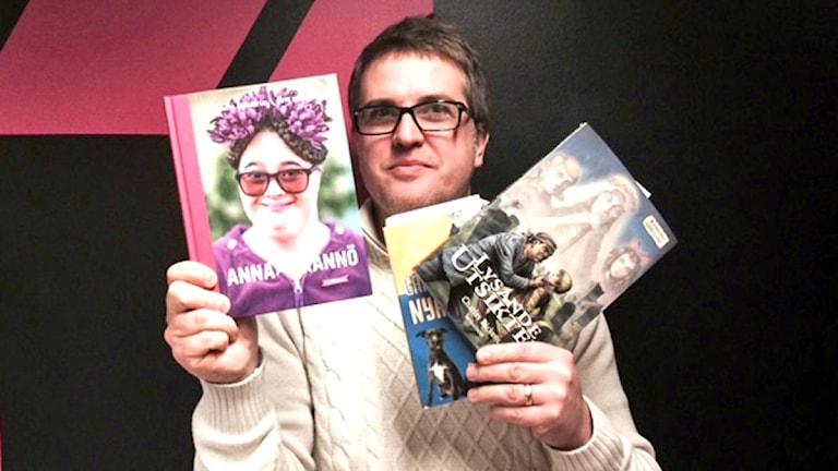 Mattias håller upp tre böcker.