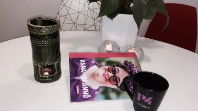 Boken ligger på ett bord. Bredvid finns en kaffekopp och tända ljus.
