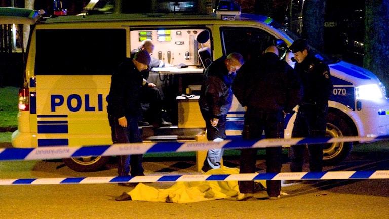 Den döda personen ligger på marken och har en filt över sig. Bredvid står flera poliser och en polisbil.