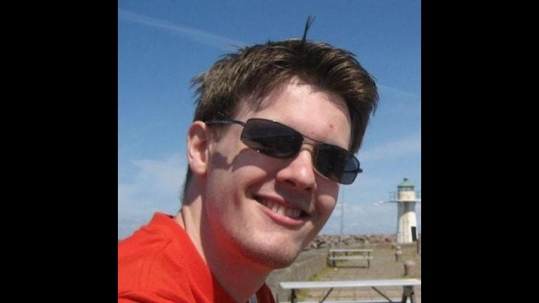 En kille i kort mörkt hår, med solglasögon och en röd t-shirt