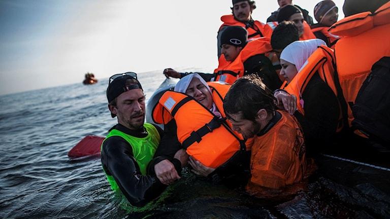 En går ner i vattnet från båten. Hon ser rädd ut. Hon får hjälp av två män.