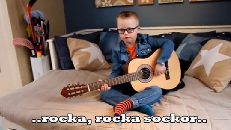 Han spelar gitarr och sjunger.