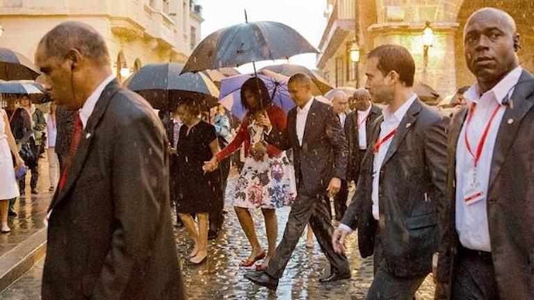 Människor med paraplyer promenerar i Havanna