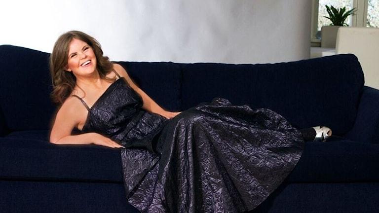 Hon har en elegant klänning på sig och ligger på en soffa.