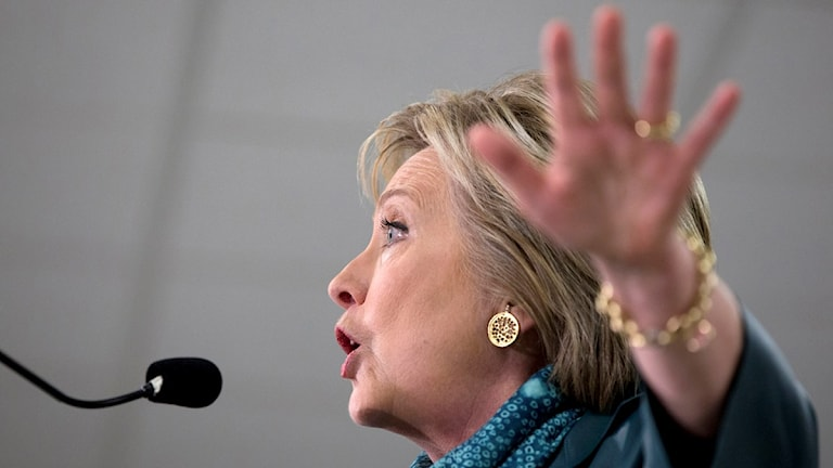 Hillary pratar och gestikulerar med handen.