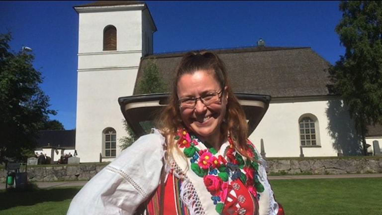 Anna har en folkdräkt på sig och står framför en kyrka.