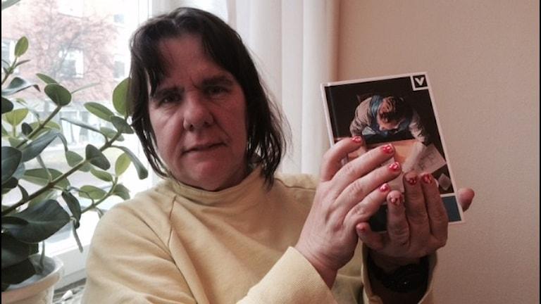 Maritha Gustafsson håller upp boken.