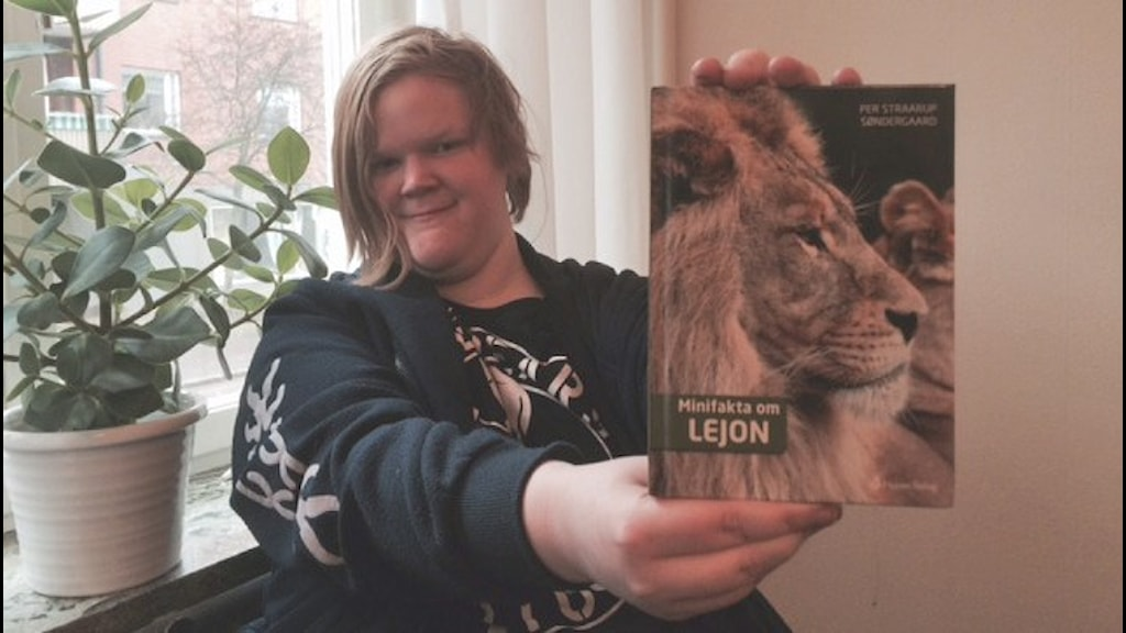Sandra håller upp boken. På bokens framsida syns en lejonhane med en stor man.