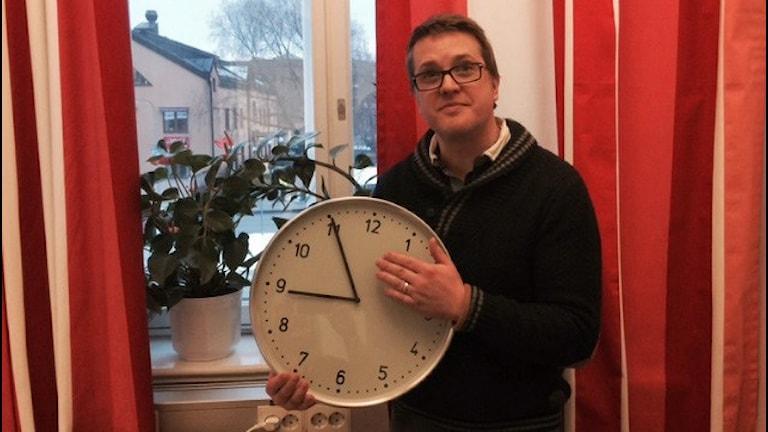 Mattias håller upp en stor klocka.