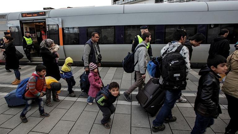 Flera flyktingar på en tågstation. Flera är barn som bär på väskor.