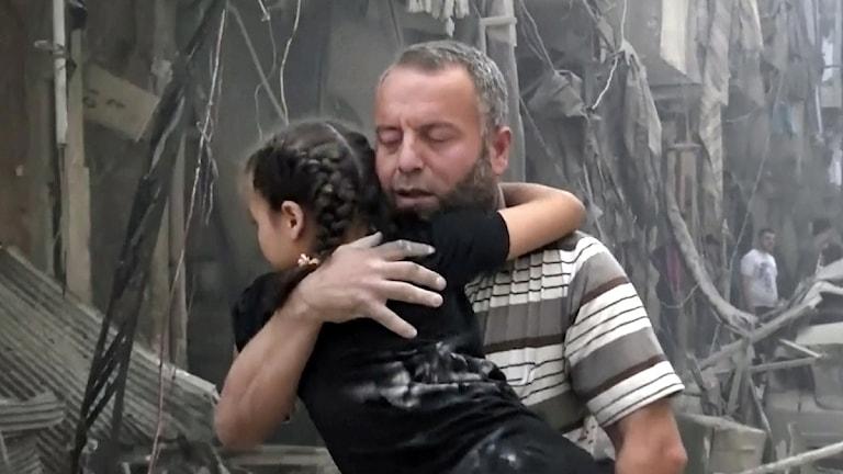 En man bär en flicka. Bakom dem syns förstörda hus.