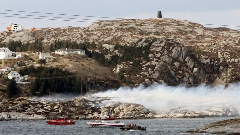 Vita hus är byggda på den kala ön. Vit ryk stiger upp från olycksplatsen.