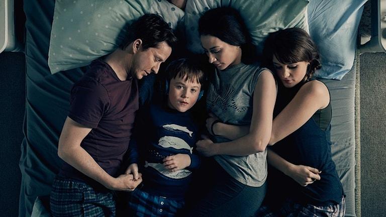 Joe omgiven av sin familj. Joe har blå hörlurar på sig.