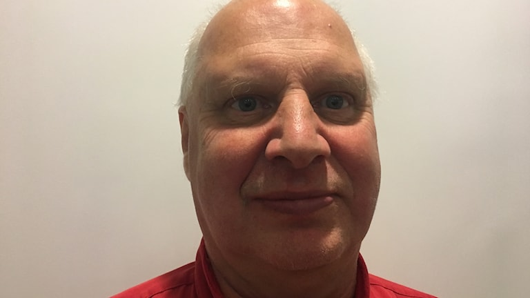 Fotot visar en man i röd t-shirt som ler.