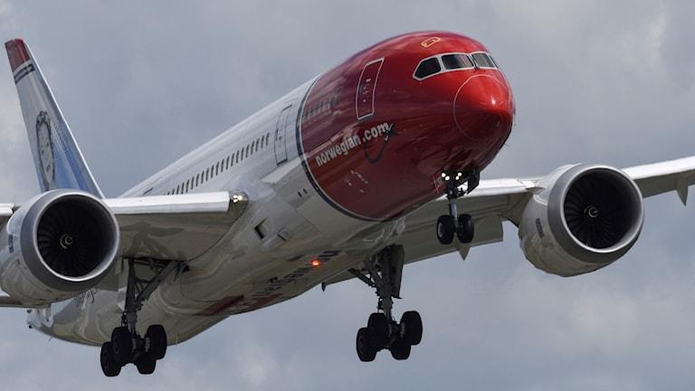 Flygplanet är i luften. Nosen är röd och resten av planet är vitt.