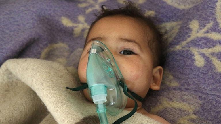 Barnet har en mask för ansiktet för att kunna andas.