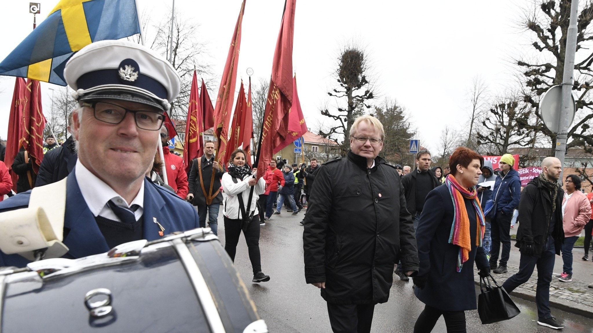 På fotot syns röda flaggor och en trumslagare klädd i blå uniform. I mitten går Peter Hultqvist, klädd i kostym.