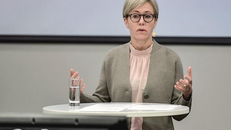 På bilden syns en blond kvinna med glasögon vid ett bord, hon står upp och håller ut händerna.
