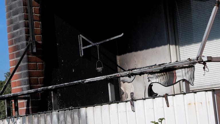 På fotot syns en balkong med ett svart sönderbränt solskydd.