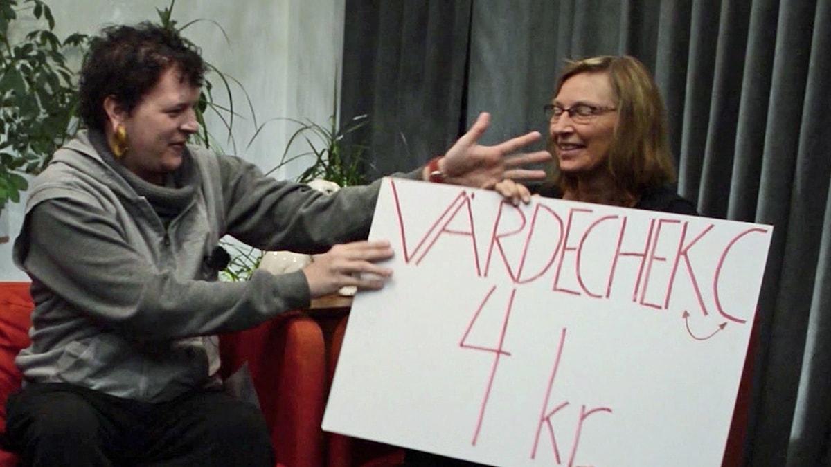 """På fotot får Carina får en jättestor papperslapp där det står """"Värdecheck 4 kronor""""."""