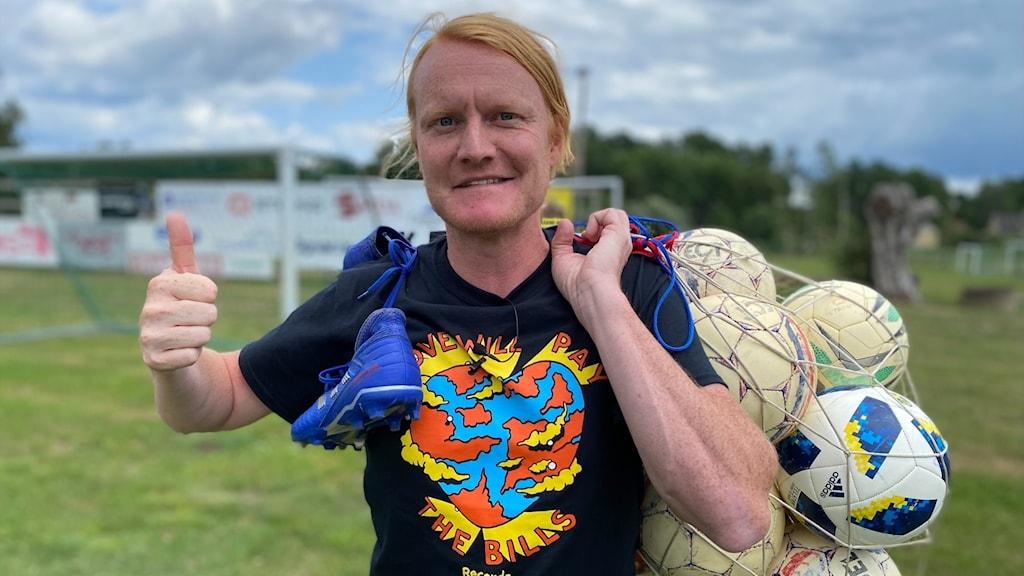 En rödblond man med svart t-shirt visar tummen upp. Han håller ett nät med fotbollar i andra handen.