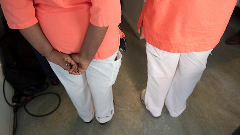 Två kvinnor har vita byxor och tröjor med orange färg.