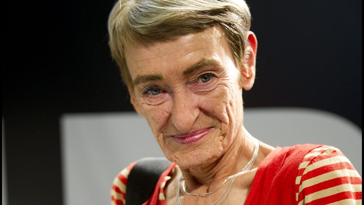 På bilden syns en kvinna som ler. Hon har kort grått hår.