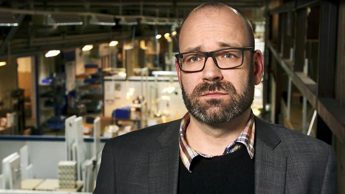 Stefan har skägg och glasögon. Han är klädd i en skjorta med en tröja över och sedan en kavaj. Bakom honom syns en stor hall inne i fabriken.