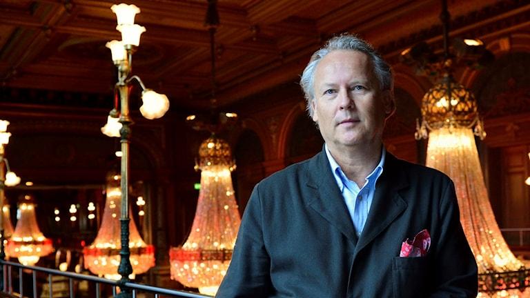 På fotot står Klas Östergren i ett pampigt rum med stora glaskronor som lampor i taket.