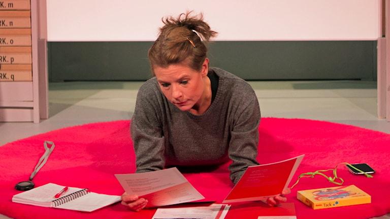 På fotot ligger en kvinna på mage och läser ett papper. På golvet ligger ett tidtagharur, ett anteckningsbok, böcker, en chokladask och en mobiltelefon.