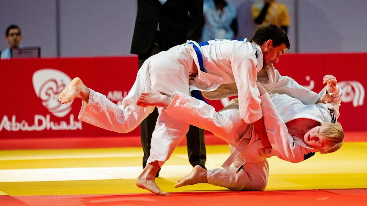På fotot syns hur två personer är klädda i vita judokläder. De försöker brotta ner varandra på marken.