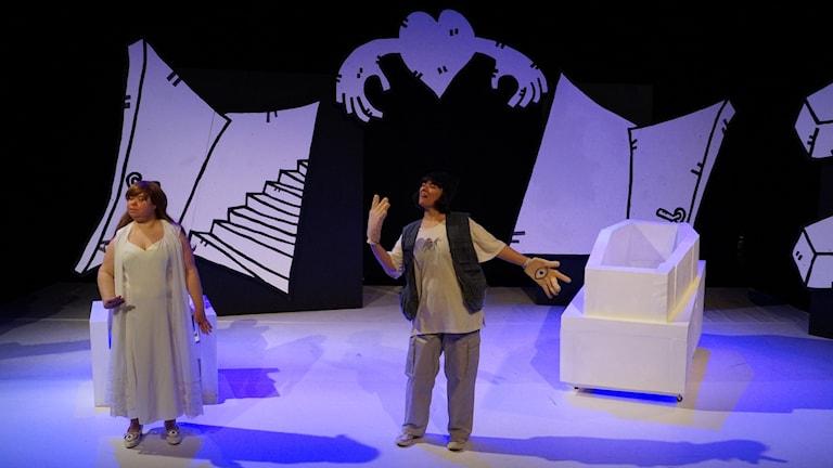 På scenen syns en vit kista och två kvinnor. Den ena kvinnan har stora handskar med ditmålade ögon på.