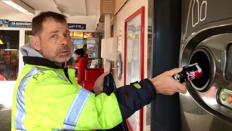 På fotot stoppar per in en läskburk i en pantmaskin. Han är klädd i gula arbetskläder med reflexer på.