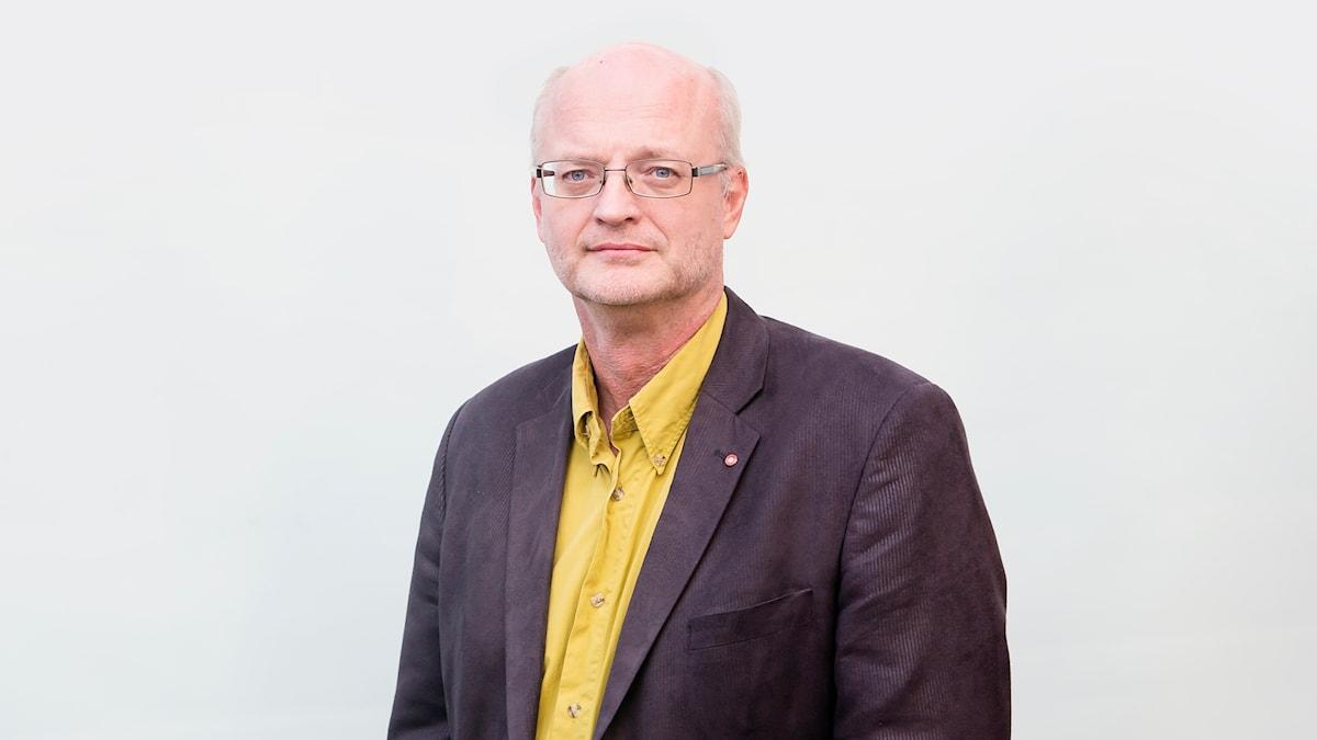 En man i glasögon, gul skjorta och svart kavaj.