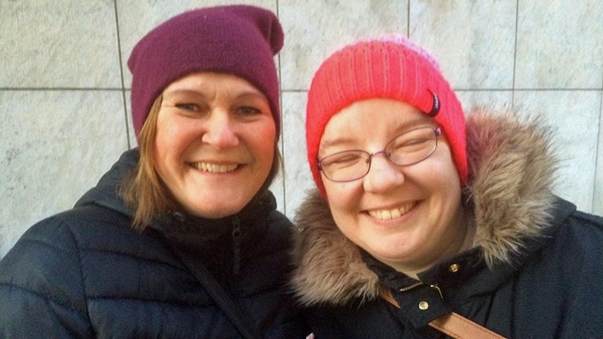 På fotot står Ingrid och Kati. Båda har mörka täckjackor och mössa på huvudet.