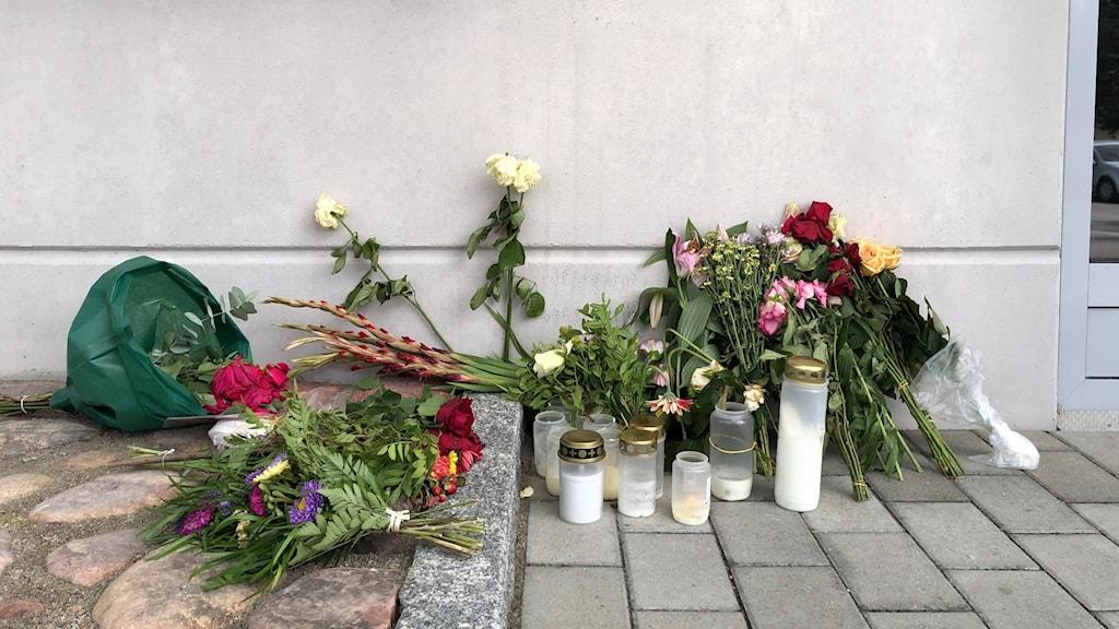 Blommor och ljus utanför bostaden där den personliga assistenten misstänks ha mördats.