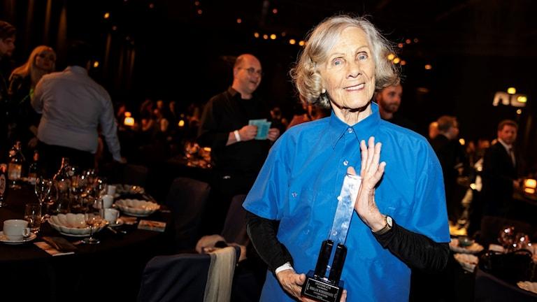 På fotot syns Gullan Bornemark som håller upp priset hon fick på Grammisgalan. Bakom henne syns andra gäster på festen och dukade bord.