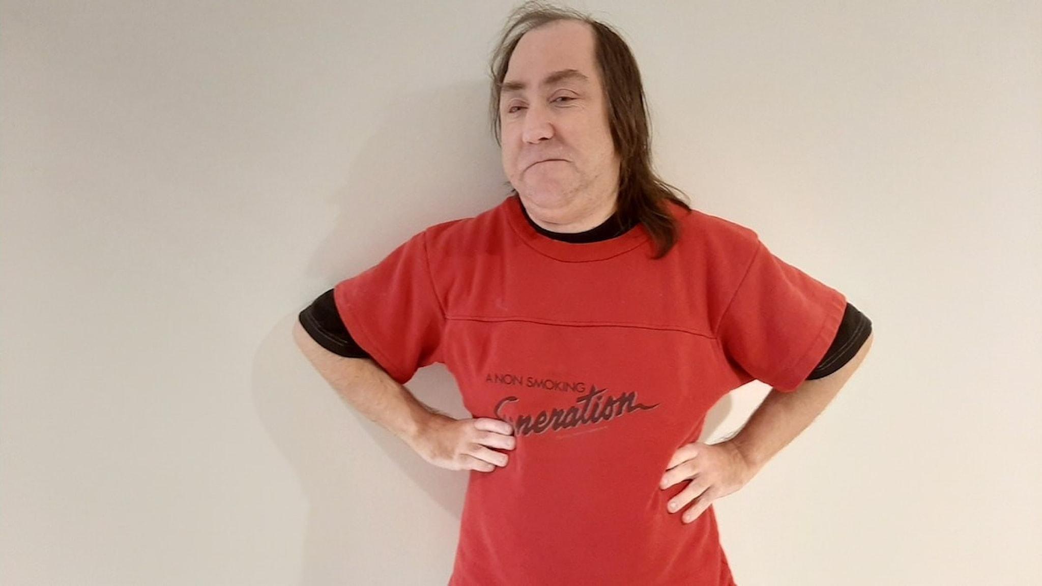 På bilden ser man en man med långt hår och klädd i en röd tröja.