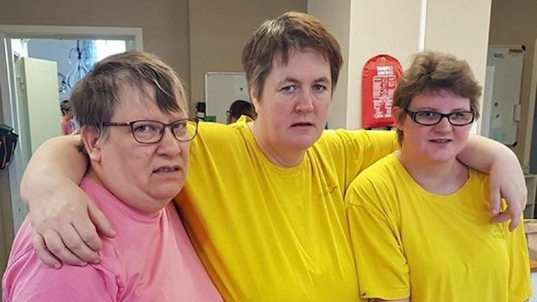 På fotot syns tre kvinnor. Deras arbetskläder är T-shirts i färgerna gult eller rosa.