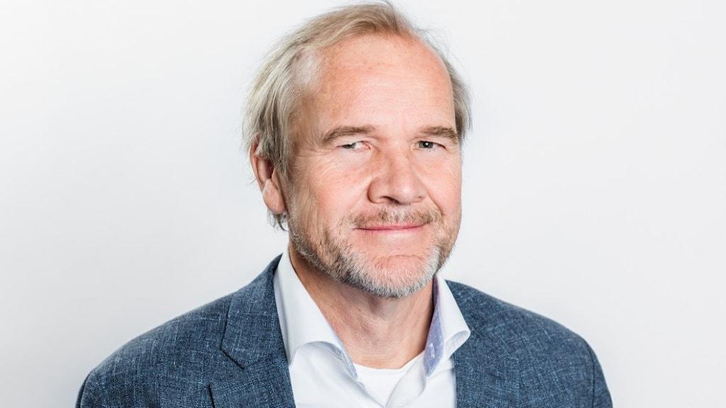 På fotot syns Anders lago. Han är blond och har skägg. Han är klädd i blå kavaj och ljusblå skjorta, men har ingen slips.