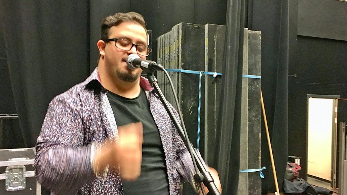 På fotot sjunger Derun och svänger med armen i takt till musiken.