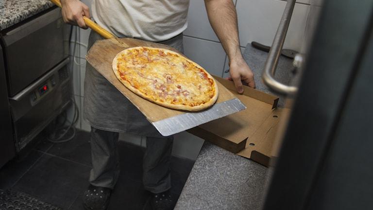 På fotot syns hur en man lägger ner en färdig pizza i en kartong.